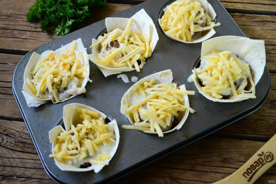 Сверху полейте соусом и присыпьте натертым на крупной терке сыром. Отправьте в духовку на 15-20 минут.