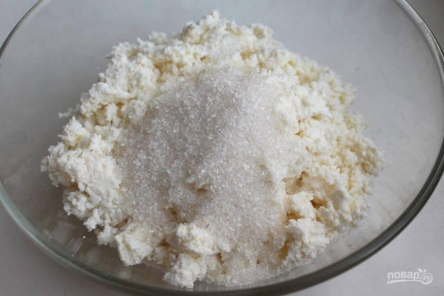 Соедените в миске творог и сахар.