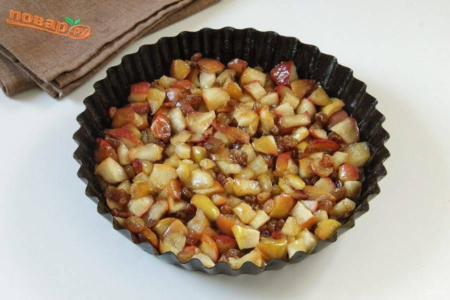 Дно формы для выпечки застелите пергаментом и смажьте маслом. Выложите ровным слоем яблоки с изюмом.