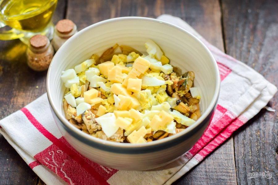 Добавьте в салат яйцо и нарезанный кубиками твердый сыр.