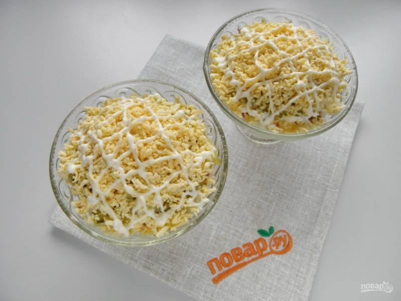 Сделайте пушистую шубку салату, для этого покройте его натертыми желтками. Сделайте майонезную тонкую сеточку.