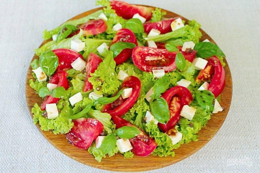 Добавляем в салат листочки базилика и поливаем все заправкой.