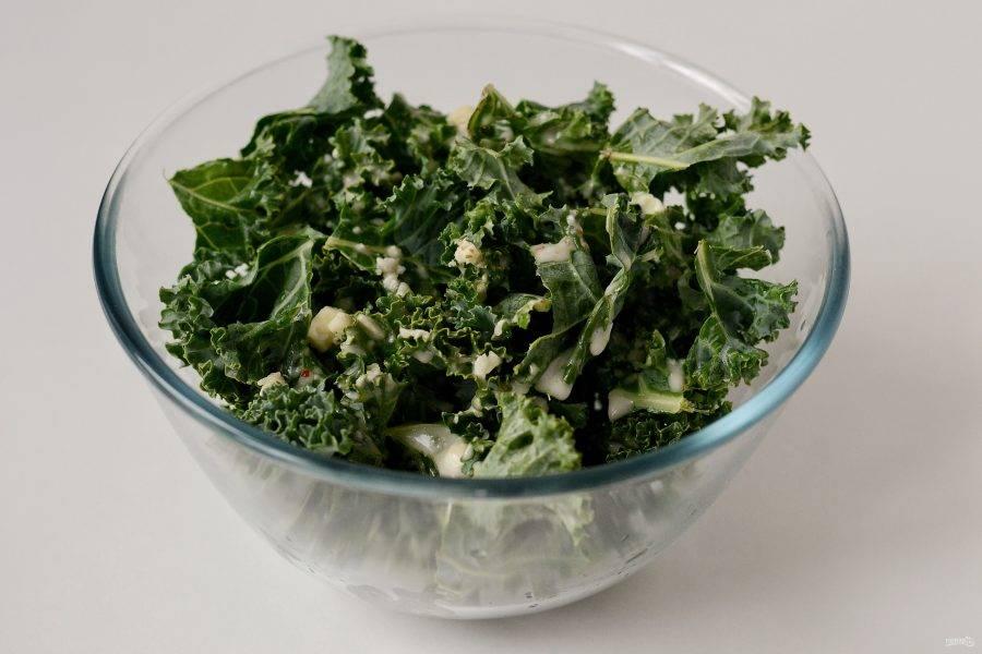 Полейте листья кейла заправкой. Начните интенсивно сжимать листья салата, чтобы они стали мягче.