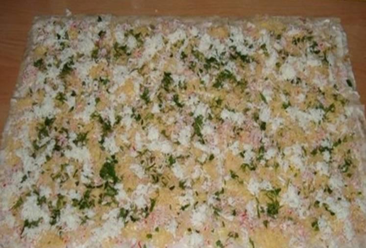 На майонез выкладываем яйца, сыр, крабовые палочки и зелень. Солим и перчим по вкусу, также можно добавить измельченный чеснок.