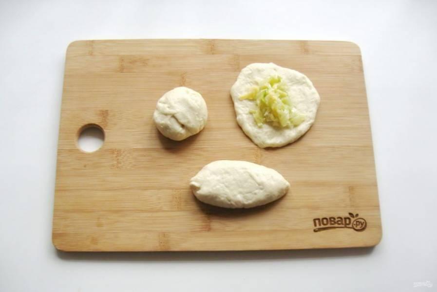 Когда тесто подойдет, достаньте его из миски и обомните. После разделите на шарики весом 50-60 грамм. Каждый шарик раскатайте в лепешку, на которую выложите начинку. Слепите края лепешки, образуя пирожок.