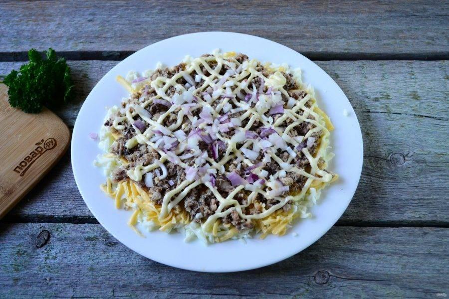 Луковицу мелко порубите ножом или измельчите блендером, выложите сверху на салат. Предварительно репчатый лук можно замариновать в уксусе и лимонном соке.