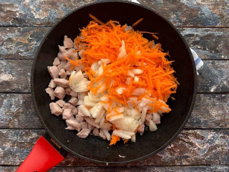 К мясу добавьте мелко нарезанный лук и тертую морковь. Хорошо все перемешайте и обжаривайте 5-10 минут.
