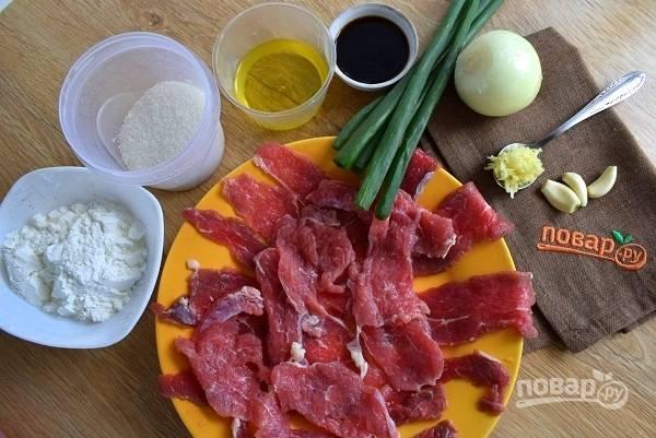 Подготовьте необходимые ингредиенты. Мясо нарежьте поперек волокон очень тонкими ломтиками. Лук и чеснок помойте, чеснок очистите.