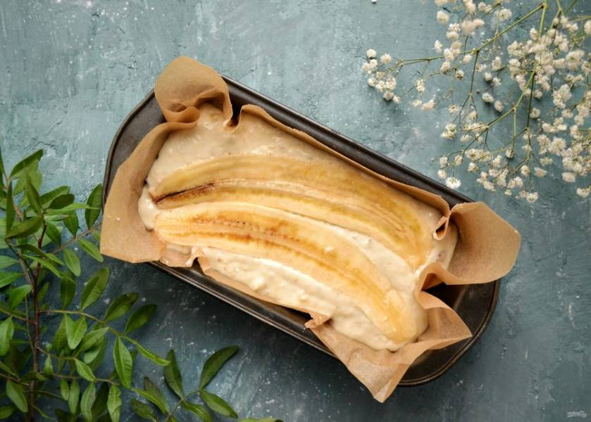 Если вы используете металлическую форму для выпечки, то застелите её пергаментом. Так кекс будет проще достать. Равномерно распределите тесто по форме, а сверху положите половинки банана. Чтобы они лучше закрепились, немного вдавите их в тесто. Выпекайте кекс в духовке при 180 градусах 45 минут.