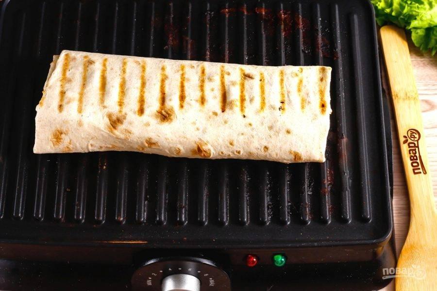 Смажьте их оставшимся майонезом, заверните начинку в лаваш в виде рулета. Прогрейте электрогриль или сковороду-гриль и выложите на нее лаваш. Поджарьте его до румяности примерно 2-3 минуты.
