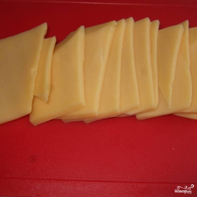 Сыр нарезаем тонкими пластинками.