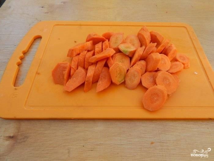 Морковь промойте, очистите. Нашинкуйте её кружками. Добавьте в казан спустя 10 минут после лука. Также добавьте 3 измельчённых зубчика чеснока.
