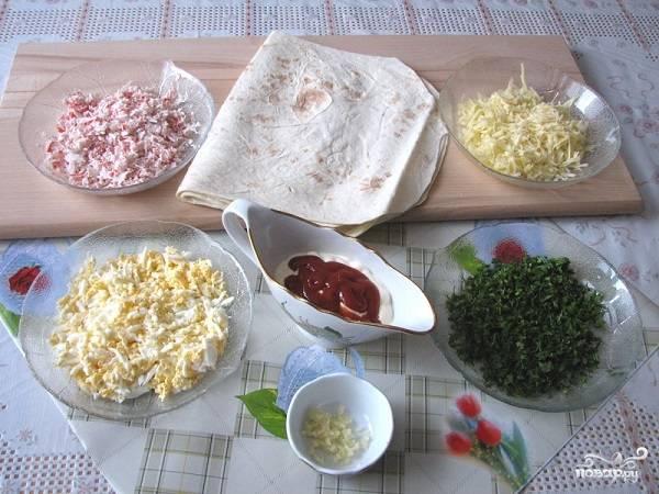 2. Яйца предварительно отварите вкрутую, остудите и очистите. Натрите на мелкую терку вместе с сыром и крабовыми палочками. Пропустите через пресс чеснок. Измельчите зелень. В качестве соуса в данном случае используется майонез с кетчупом — вариант на скорую руку.