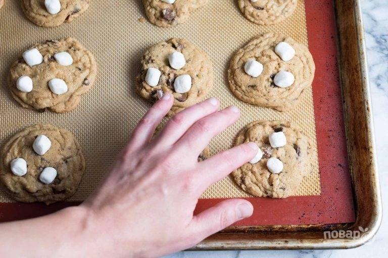 12.Запекайте печенье в разогретом до 190 градусов духовом шкафу в течение 10 минут, затем достаньте его и в каждое добавьте по 3-4 маршмеллоу. Отправьте еще на 2-3 минуты в духовку.