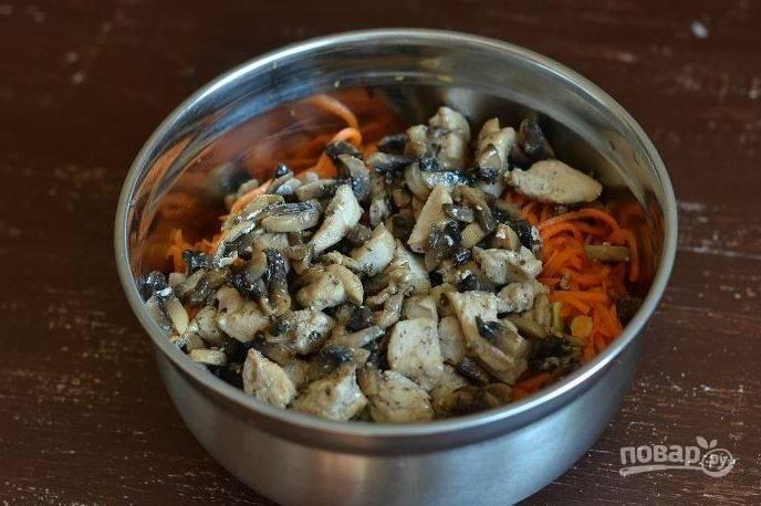 Затем добавьте в салатник корейскую морковь. Если она слишком длинная, то для удобства ее можно порезать. Поверх моркови выложите обжаренные грибы с курицей.