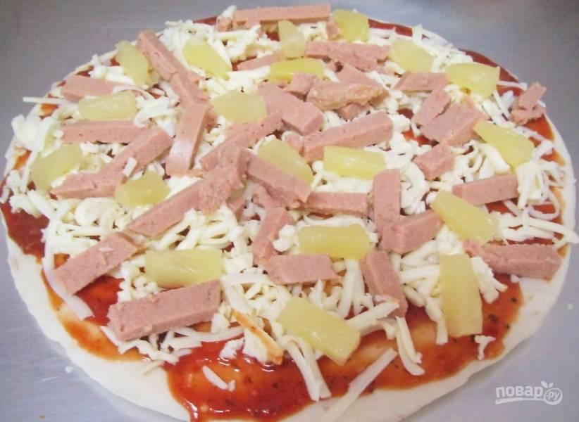 Натрите сыр, а ветчину и ананасы порежьте небольшими кусочками. Выложите эти продукты на пиццу.