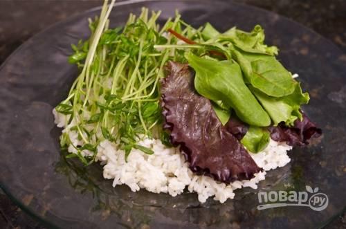 На порционную тарелку положите рис, салатную смесь.