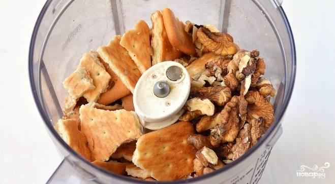 Возьмите чистую и сухую чашу для блендера, положите в нее грецкие орехи. К ним добавьте печенье, поломанное руками. Взбейте хорошенько, чтобы песочно-ореховая масса стала однородной.