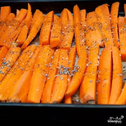 3. Противень застелите пергаментной бумагой. Выложите морковь. Сбрызните ее оливковым маслом, посыпьте солью, перцем и сушеной лавандой.