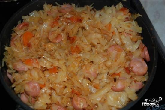 Добавляем к капусте нарезанные сосиски и спассерованные лук и морковь. Тушим до готовности на медленном огне ещё минут 10.