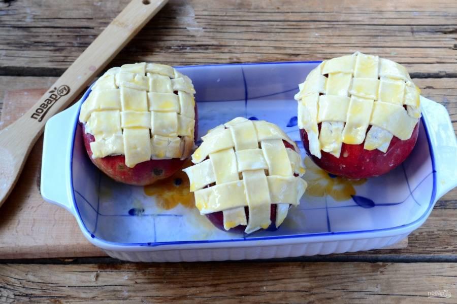 Смажьте тесто взбитым яйцом, яблоки поставьте в форму для выпекания, в которую налейте 100 мл воды. Отправьте яблоки в духовку на 20-30 минут (температура — 180 градусов). Время выпекания зависит от сорта яблок. Плюс, конечно же, смотрите, чтобы тесто пропеклось, стало золотистым и не сгорело.