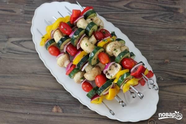 4. Полейте все оливковым маслом и аккуратно перемешайте. Разместите овощи и грибы на шампурах, чередуя.