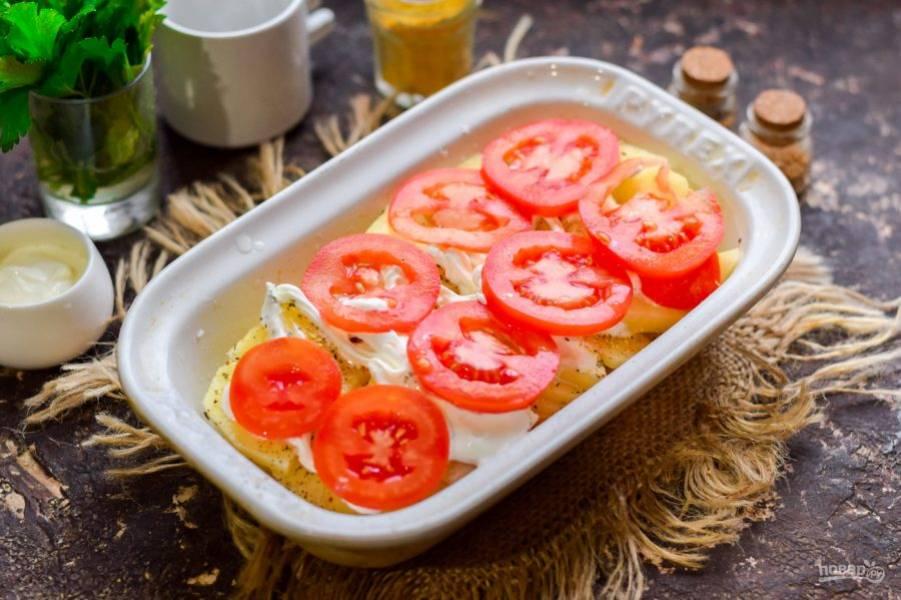 Далее смажьте картофель сметаной. Помидоры сполосните и просушите, нарежьте пластинами. Выложите пластины помидоров поверх картофеля.