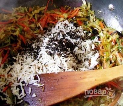 Рис промойте и отварите до полной готовности согласно рецепту на упаковке. Выложите отваренный рис к овощам и добавьте туда же кунжут. Чтобы блюдо выглядело более оригинальным, лучше выбирать черный кунжут, хотя семена белого цвета также подойдут.