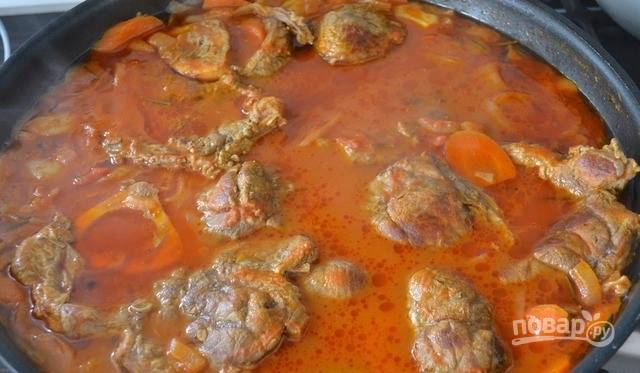 В сковороду к остальным ингредиентам выложите заранее обжаренное мясо. Долейте воды столько, чтобы она полностью покрыла мясо. Накройте крышкой, уменьшите огонь и тушите около двух часов, доливая по мере необходимости жидкость.