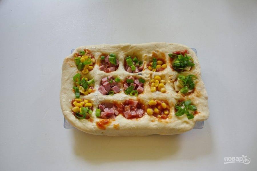 Ячейки формы  с тестом наполните томатным соусом, рубленой зеленью, кукурузой, рубленой ветчиной и другой начинкой, что у вас найдется. Начинку можно укладывать рядами или класть в каждую ячейку тот вид начинки, который нравится вам. Каждую ячейку присыпьте натертым сыром.