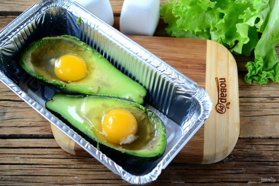 Положите половинки авокадо в форму для запекания. Выньте еще немного мякоти в середине, чтобы сделать углубление для яйца побольше. В каждое углубление разбейте яйцо, посолите и поперчите по вкусу.