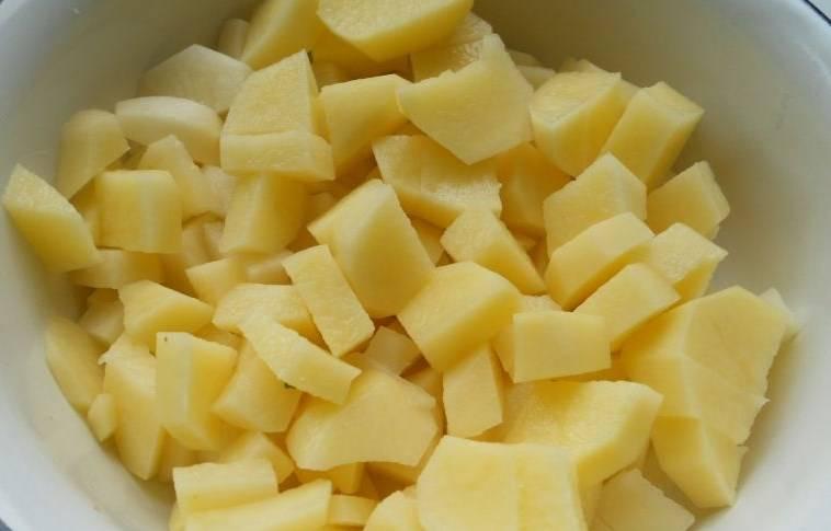 Картофель очистить и нарезать кусочками. Выложить его в кастрюлю к гороху.