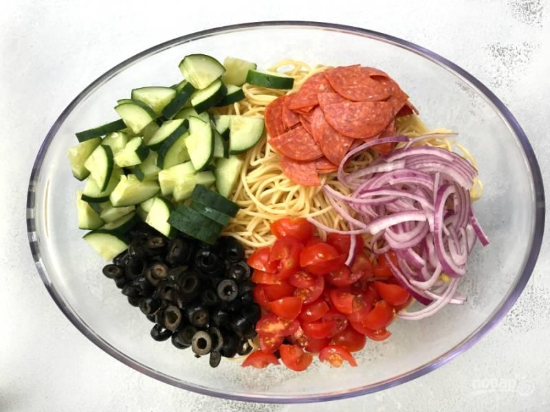 2. Нарежьте оливки колечками, помидоры и колбасу — половинками, огурец — кубиками, лук — соломкой.