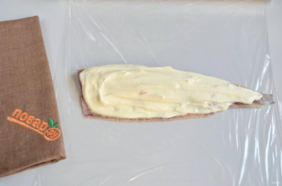3. На пищевую пленку положите половинку рыбного филе. Хорошо смажьте плавленным сыром.
