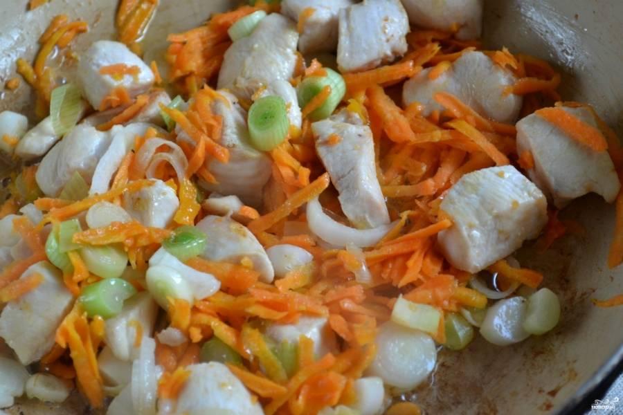 На разогретом подсолнечном масле поджарьте кусочки курицы (примерно 5 минут), посолите. Потом добавьте лук, перемешайте. Потушите пару минут. Добавьте морковь, всё хорошенько перемешайте и томите ещё 5 минут.