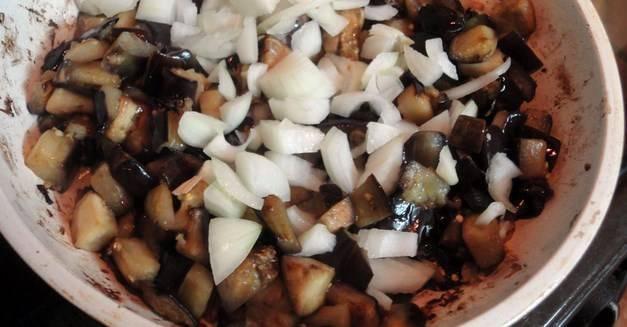 Минут через 5 добавьте к баклажанам мелко нарезанные лук и чеснок. Чеснок можно либо мелко порубить ножом, либо пропустить через чеснокодавку. Перемешайте все, жарьте до размягчения овощей. Посолите.