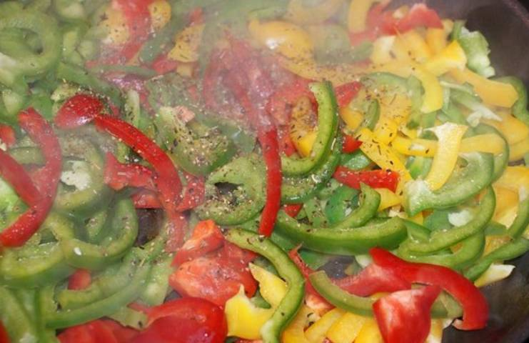 Болгарский перец нарезаем соломкой и обжариваем на сковороде, добавив майоран, перец, соль и тимьян.