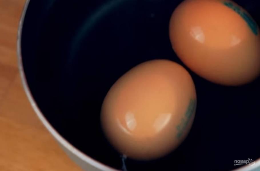 2. Затем приготовьте соус. Для этого проколите снизу иголкой два яйца и опустите их в закипевшую воду на 2 минуты.