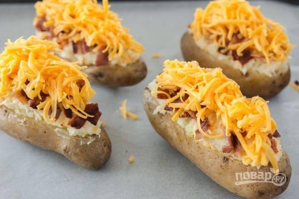 4.Наполните картофель начинкой и посыпьте обжаренным беконом, поверх добавьте оставшийся сыр и отправьте картофель обратно в духовку еще на 15 минут.