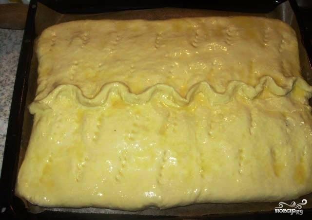 Выложите пирог на противень, смазанный растительным маслом, чтобы тесто не пристало к нему. А сам пирог смажьте желтком, чтобы при выпекании на тесте образовалась румяная хрустящая корочка.