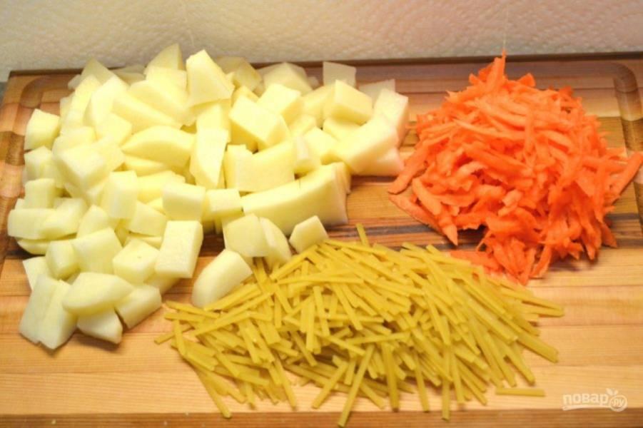2.Почистите морковь и картофель. Порежьте картофель средними кусочками, натрите морковь на средней терке, поломайте макароны.
