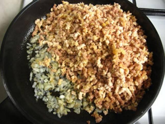 Полученный фарш добавьте на сковороду к луку, добавьте немного растительного масла  и слегка обжарьте – не более 5 минут.