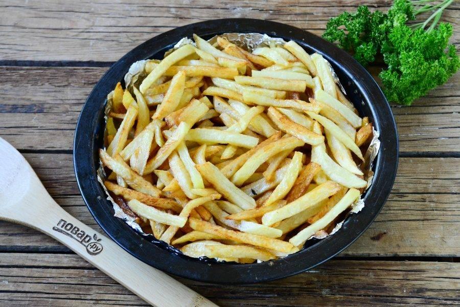 Картофель фри посолите и поперчите по вкусу, выложите в форму для запекания диаметром примерно 22 см.