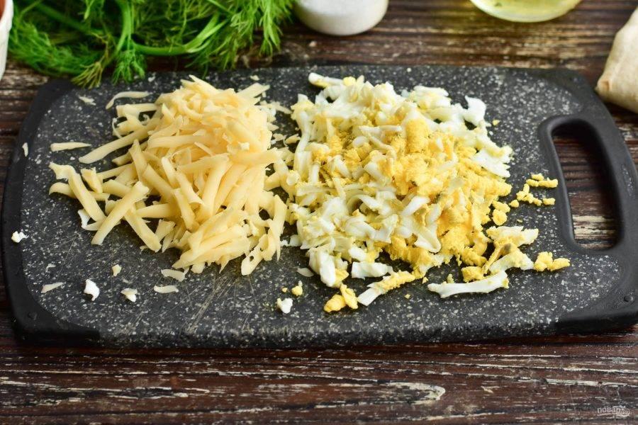Натрите на крупной терке вареное куриное яйцо и твердый сыр.