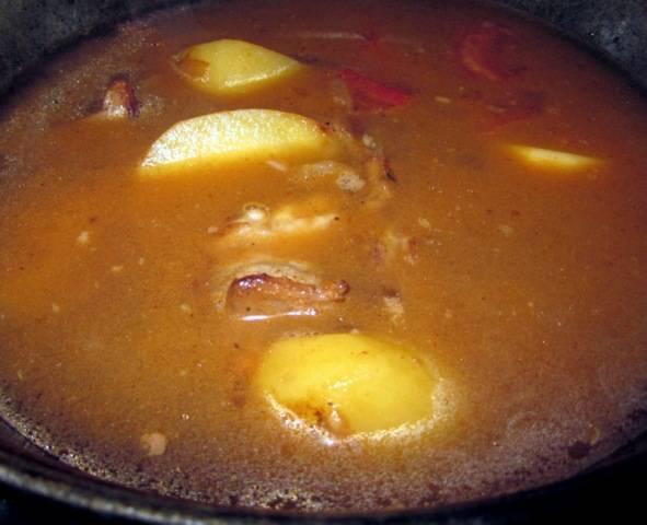 После того, как помидоры потушатся-пожарятся минутки 2, заливаем в казан воду. ее должно быть столько, чтобы она слегка покрыла содержимое казана. После того, как наш суп закипит, добавляем все специи кроме зелени и уменьшаем огонь. Варим минут 30-40.  Затем добавляем измельченный чеснок и даем супчику настояться. Перед подачей посыпать нарубленной зеленью.
