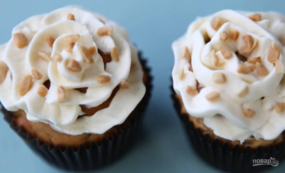 5. Сверху украсьте кремом: смешайте для этого пасту «Филадельфия», масло сливочное и сахарную пудру. Посыпьте орехами. Кексы готовы, приятного аппетита!