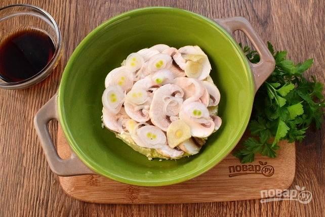 Фету поместите в форму для запекания или фольгу. Шампиньоны, лук и чеснок нарежьте тонкими ломтиками, разместите их поверх сыра.