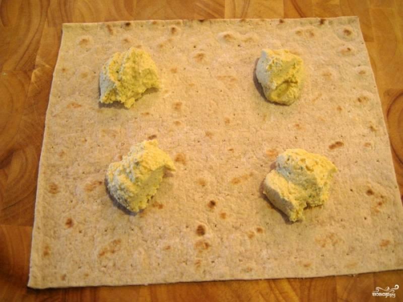 1. Расстилаем лаваш, смазываем его равномерно хумусом. Посыпаем специями.