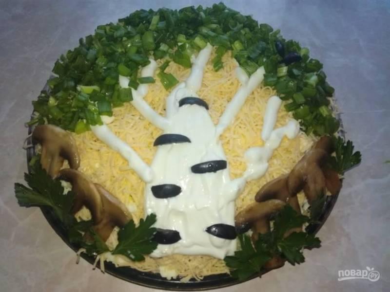 4.Отвариваю яйца и остужаю, затем измельчаю на крупной терке и выкладываю следующим слоем, смазываю майонезом. Сыр натираю на мелкой терке и посыпаю салат. С помощью майонеза, оливок, грибов, петрушки и зеленого лука украшаю салат. Настаиваю его 30 минут.