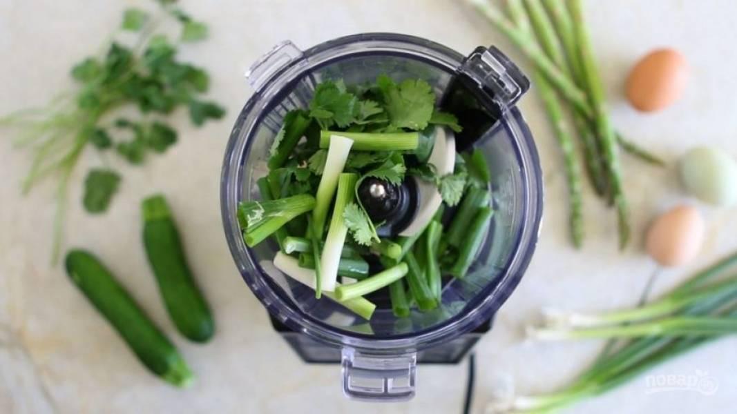 1. Для начала в блендер выложите лук, очищенный чеснок и кинзу. Измельчите овощи.